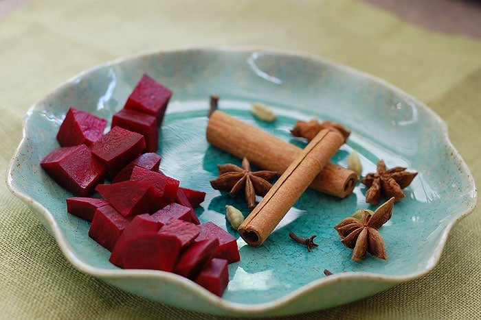 Blue pottery plate of cut beets, cinnamon sticks, cardamom pods, and star anise