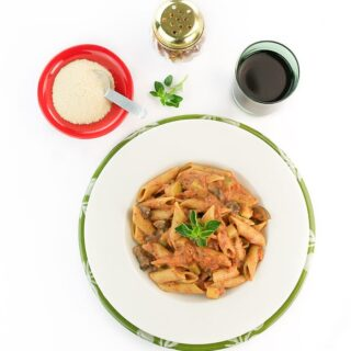 Penne pasta with vodka sauce on a white plate with a glass of red wine.