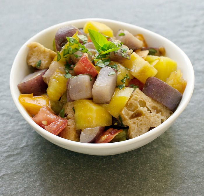 Instant Pot Potato Panzanella Salad in white bowl on a stone background.