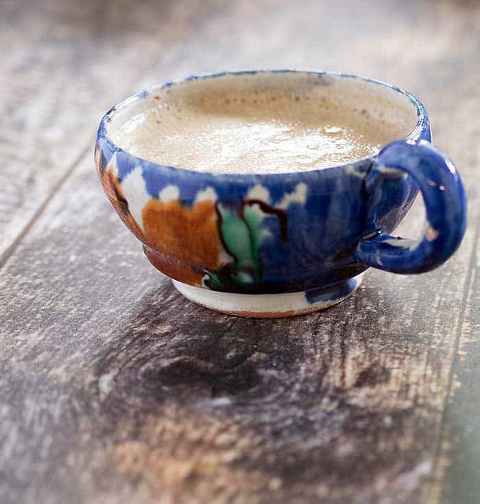 Slow Cooker vegan maple pumpkin latte in a rustic blue and orange painted pottery cup