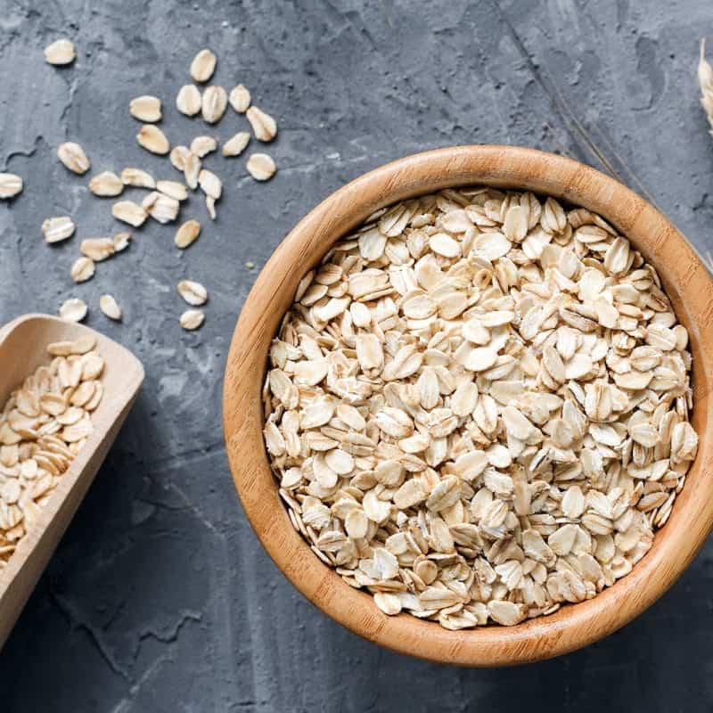 Rolled oats on a wooden bowl placed on a stone surface