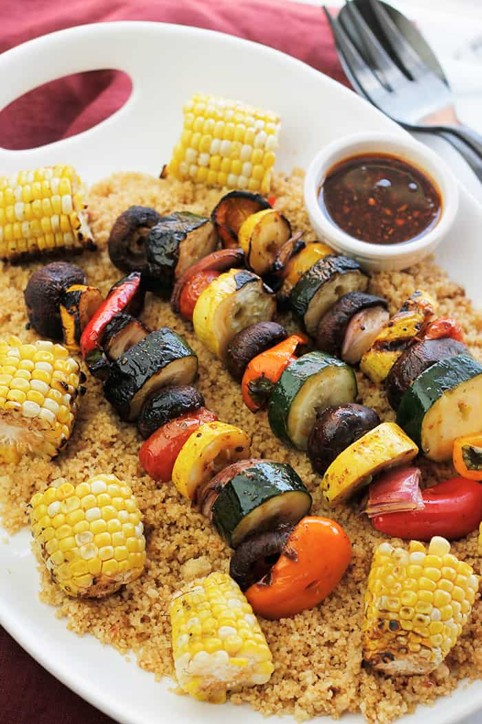 Platter of Harissa Grilled Veggie Kabobs with Corn over Couscous.
