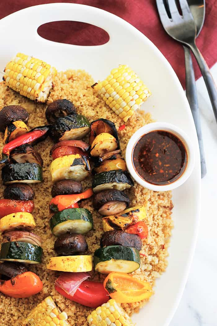 Overhead shot of Harissa Grilled Veggie Kabobs with Corn over Couscous.