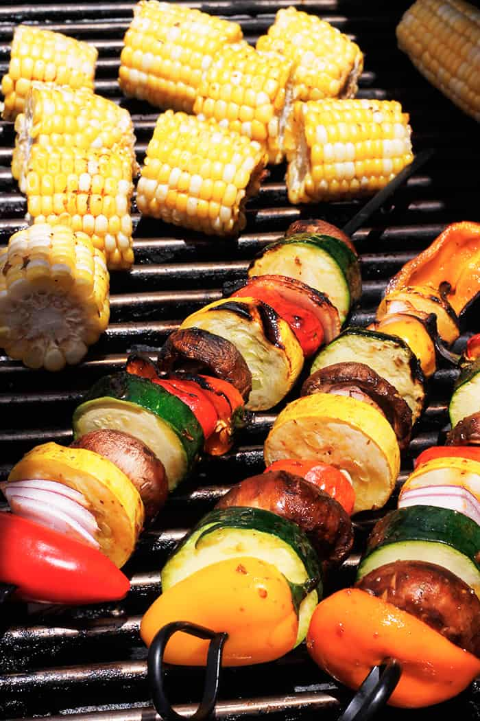 Corn on the cob and Harissa grilled Veggie Kabobs on the grill.