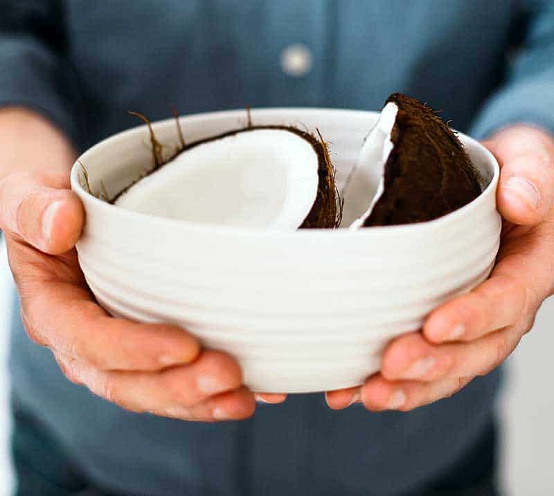 Split coconut in a white bowl held in a man's hands