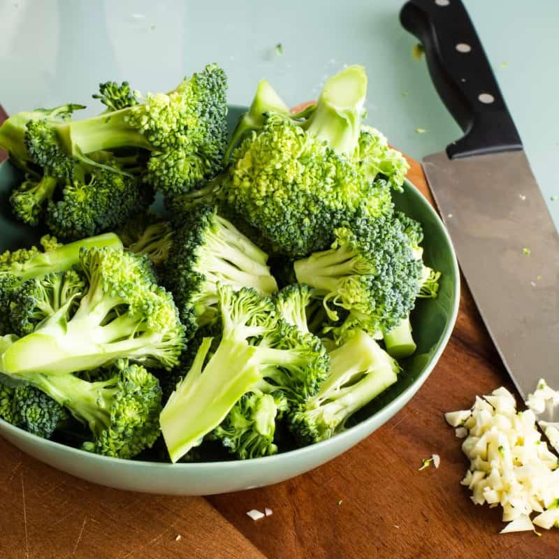 Fresh broccoli florets in a bowl on a cutting board with minced garlic