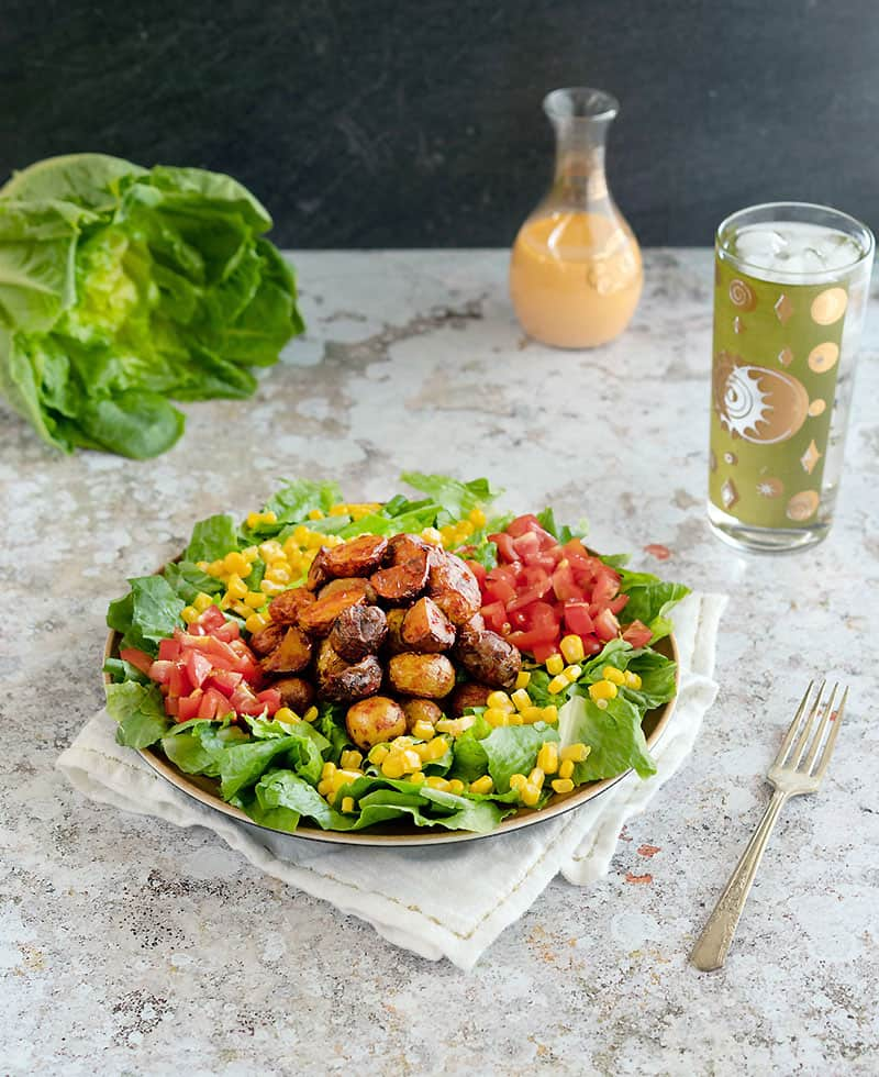 Image of salad, dressing, and drink