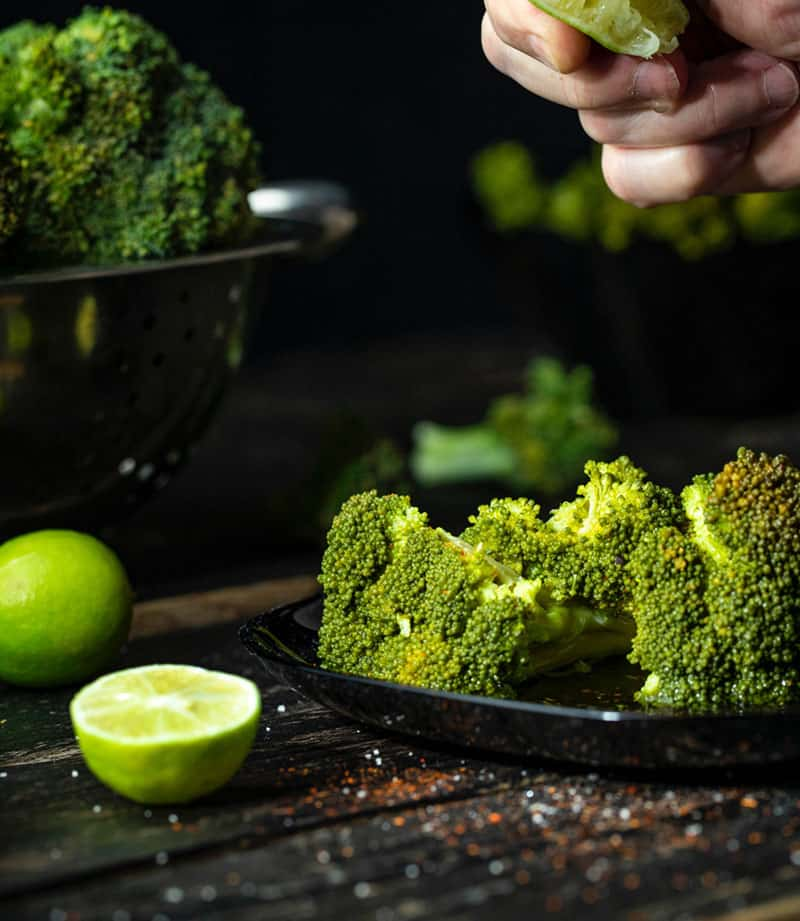 Lime being squeezed on broccoli