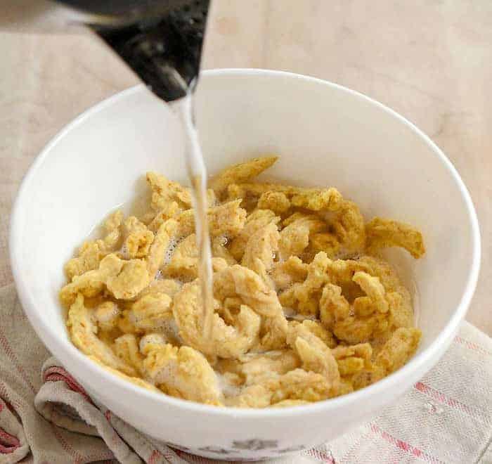 Hot water being poureed over soy curls in white bowl.