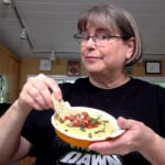 Kathy Hester dipping a tortilla chip in oat vegan queso!