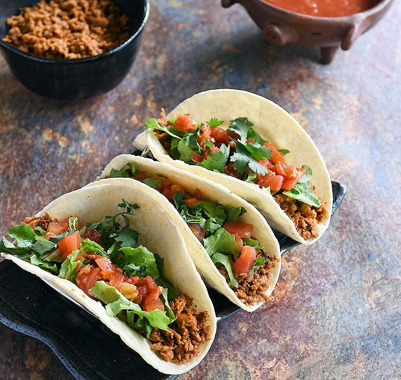 Soft tacos with minced soy curl filling topped with lettuce, chopped tomatoes, and cilantro.