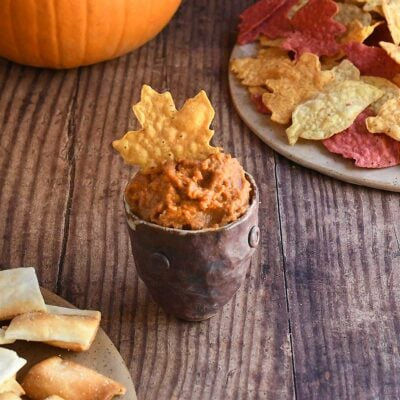 Ancho chile pumpkin hummus in a brown handforn potter bowl with a maple leaf shaped yellow tortilla chip